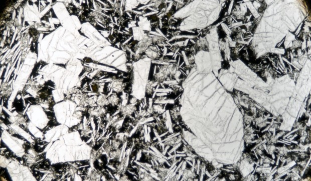 Porphyritic plagioclase  concentrated in one area of the sample occurring as glomerocrysts and individual crystals. Sample viewed in plane polarised light  (x5)