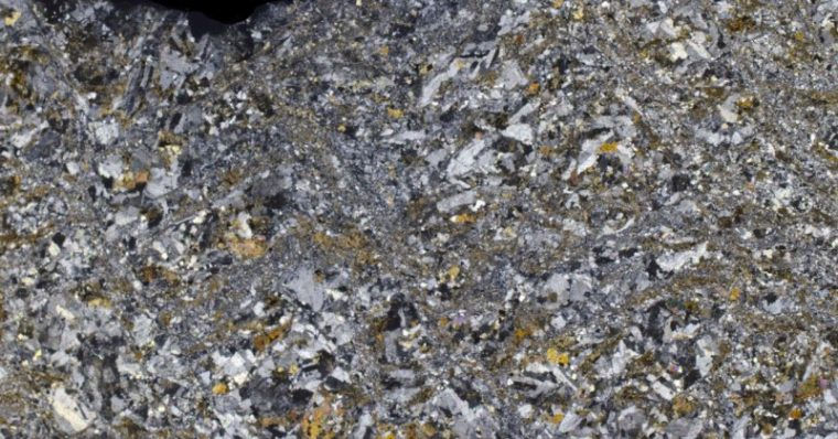 A sub-equigranular, mafic-rich granitic rock disrupted by a fine-grained intrusion that is also mafic-rich. Thin section viewed with crossed polarising filters.