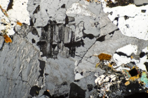 Complex inter-growth of plagioclase, potassium feldspar, quartz and biotite in a relatively unaltered rock from the summit of Hedgehope Hill viewed with crossed polarising filters.