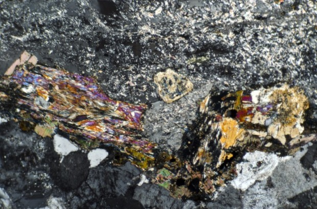 Plagioclase, pyroxene, quartz and associated alteration products in   syeno-granite  at location 3. Thin section viewed with crossed polarising filters.