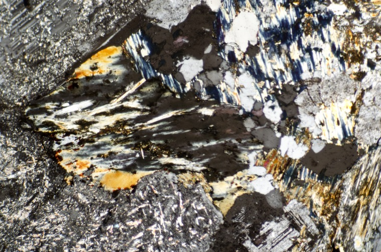Alteration products of plagioclase in syeno-granite at location 8, Harthope Linn viewed with crossed polarising filters.