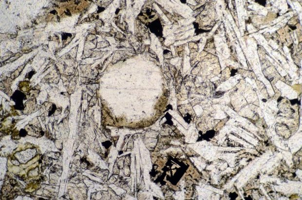 An amygdaloid in Kielderhead tholeiite basalt that is mostly filled with clear glass. Sample viewed in plane polarised light at X10