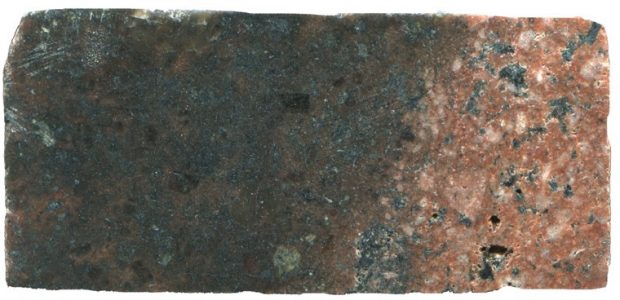 Prepared hand specimen of   syeno-granite   (red) in contact with what is probably an andesitic xenolith (black) viewed in reflected light. The sample measures 45 mm across.