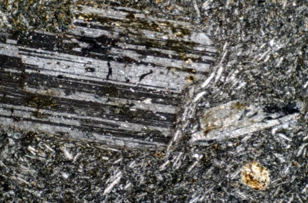 Plagioclase phenocryst in opaque-rich feldspar matrix at location 6, Harthope Linn viewed with crossed polarising filters.