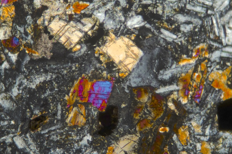 Orthopyroxene (light orange crystal at centre) and clinopyroxene (e.g. orange, red & blue crystal, below) in Acklington dyke basalt. Sample viewed with crossed polarising filters at X25