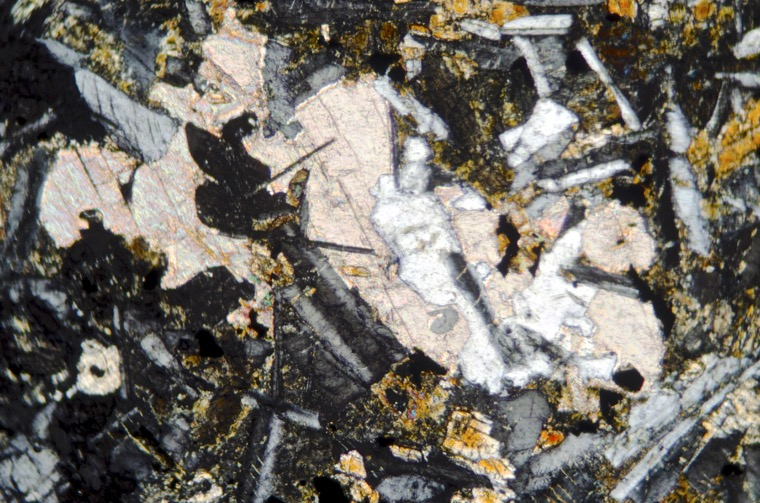 Calcite in the Acklington dyke basalt in the Hosedon Burn valley. Sample viewed with crossed polarising filters at x25