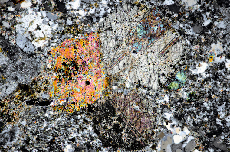 Clinopyroxene crystals in  the same fine-grained quartz-monzonite viewed with crossed polarising filters (FoV 2.5 x 1.7 mm)