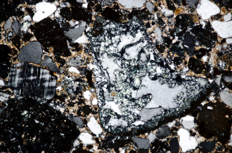 Microcline amongst lithic fragments with chlorite, quartz, feldspar with individual crystals set in a partially cabonatised ground. Sample viewed with crossed polarising filters (FoV 2.3 x 1.5 mm)