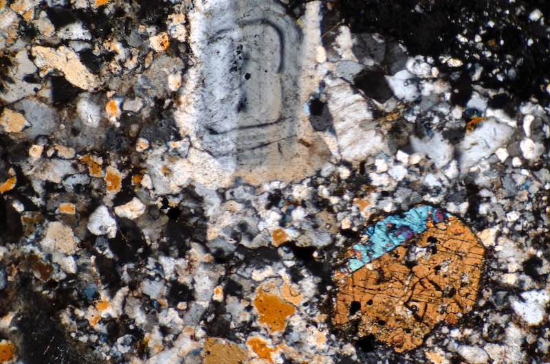 Clinopyroxene and zoned plagioclase in the finer-grained rock in the same sample, Shielcleugh Edge. Section viewed with crossed polarising filters