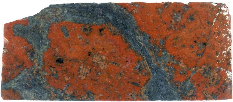 Intermingled red and black andesitic rock. Low Bleakhope (NT935154) Prepared hand specimen in ordinary reflected light (44mm across)