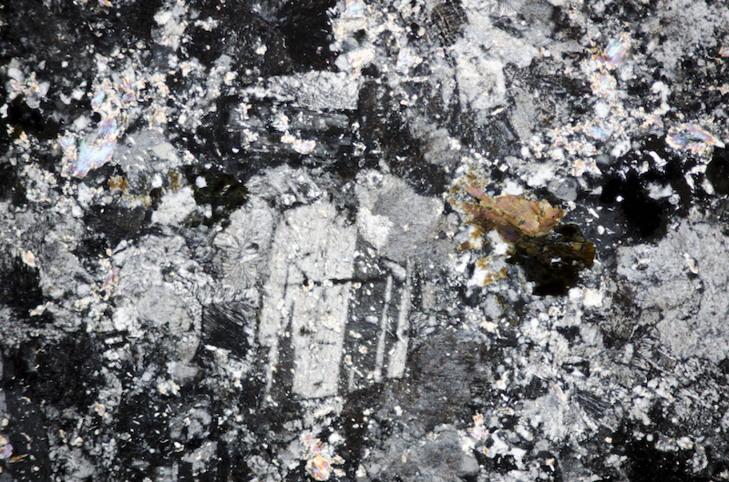 Plagioclase, mica and tourmaline with perthite in porphyry. Section viewed with crossed polarising filters (FoV 2.3 x 1.5 mm)