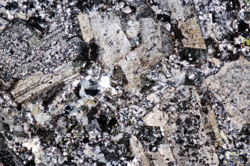 Plagioclase and sanidine phenocrysts in fine grained matrix in granitic rock, Hawsen Burn. Section viewed with crossed polarising filters (FoV 4.6 x 3.0 mm)
