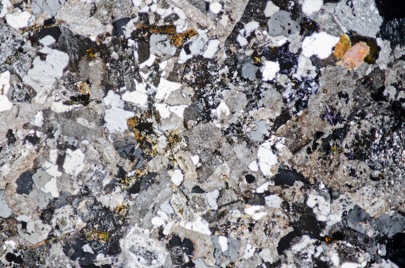 Granite at Woolhope Crag. There is little plagioclase but a lot of alkali feldspar in the rock,  chlorite, sericite and tourmaline are present.. Section viewed with crossed polarising filters FoV 4.6 x 3.0 mm)