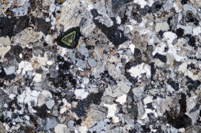 Granite on Cheviot. Contains plagioclase phenocrysts, coarsely granophyric quartz, and tourmaline. Section viewed in plane polarised light (FoV 4.6 x 3.0 mm)