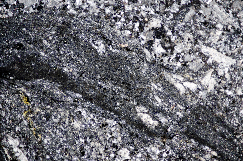 Vein of glassy, opaque-rich material in Marginal dioritic rock. Section viewed with crossed polarising filters (FoV 4.6 x 3.0 mm)