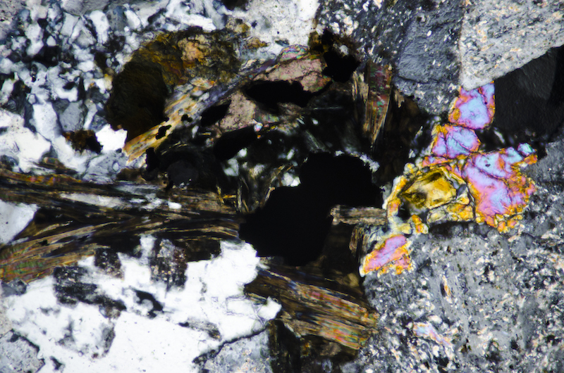 Chlorite with a mineral showing moderately high birefringence that is possibly, epidote with opaque iron titanium oxides. Section viewed with crossed polarising filters (FoV 1.2 x 0.8 mm)