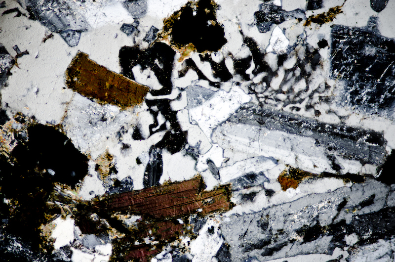 Biotite, magnetite and chlorite with quartz and feldspar in micrographic texture. Section viewed with crossed polarising filters (FoV 1.2 x 0.8 mm)