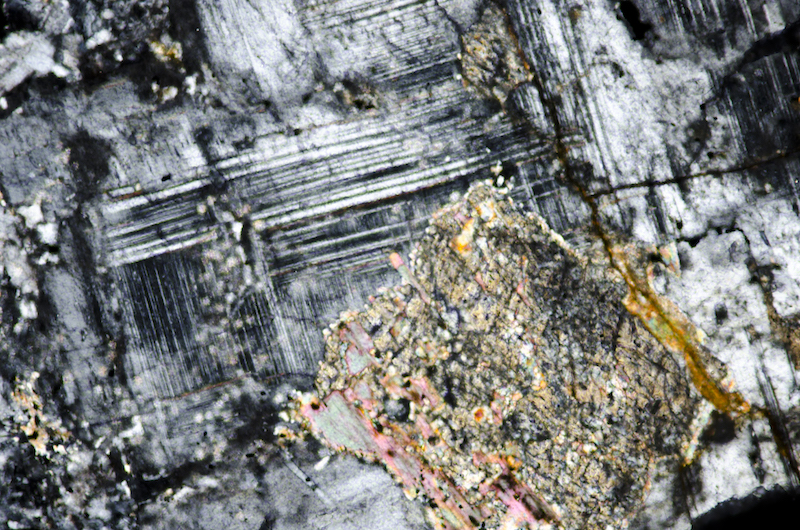 Secondary biotite forming at the edge of a corroded crystal, possibly pyroxene, enclosed in plagioclase. Section viewed with crossed polarising filters (FoV 1.2 x 0.8 mm)