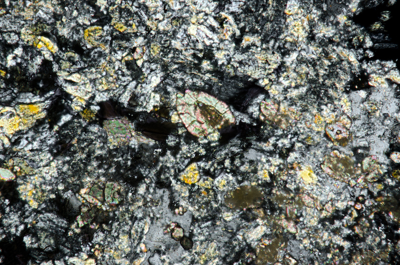 Zircon and pyroxene granules in the mafic intrusion into andesite.Section viewed with crossed polarising filters (FoV 1.2 x 0.8 mm)