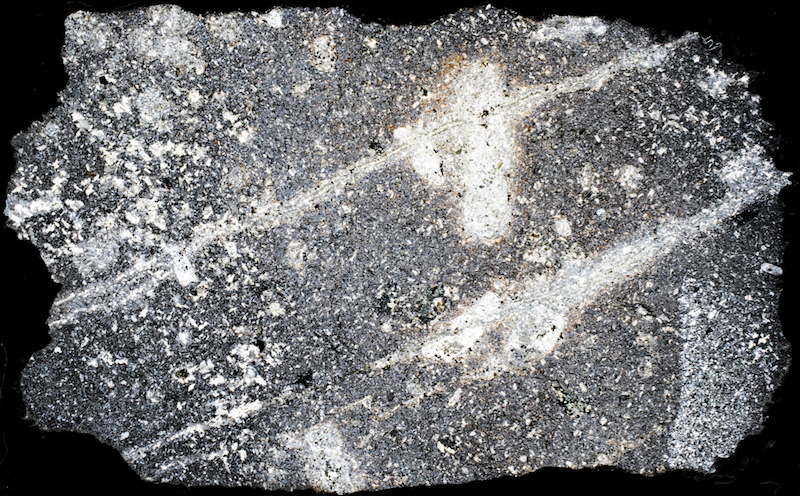 Carbonitised andesite or tuff, Breamish Valley NT937156. There is a clearly deliniated patch of quartz in the bottom right hand corner that doesn