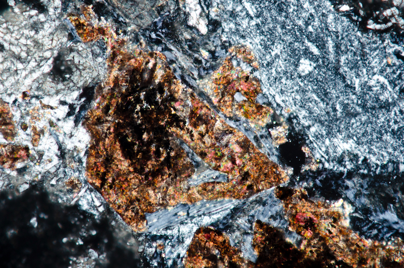 Granular clinopyroxene rimmed with chlorite. Section viewed with crossed polarising filters (FoV 0.5 x 0.3 mm)