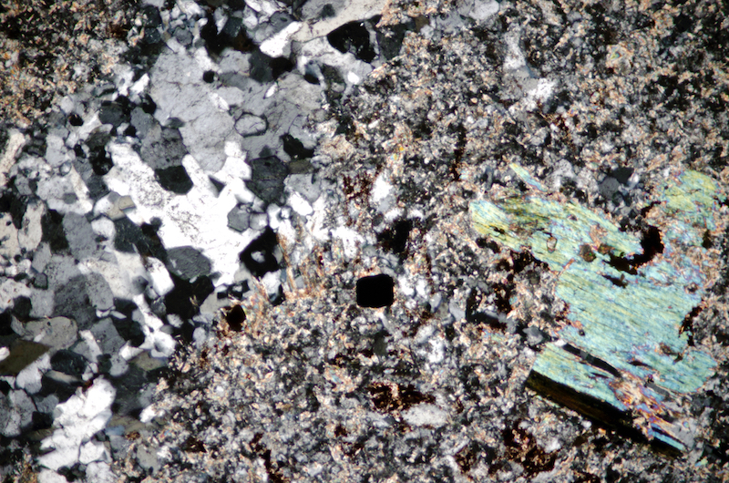 Quartz veinlet in sericitised feldspar and quartz groundmass with muscovite and tourmaline with opaques. Section viewed with crossed polarising filters (FoV 2.5 x 1.7 mm)