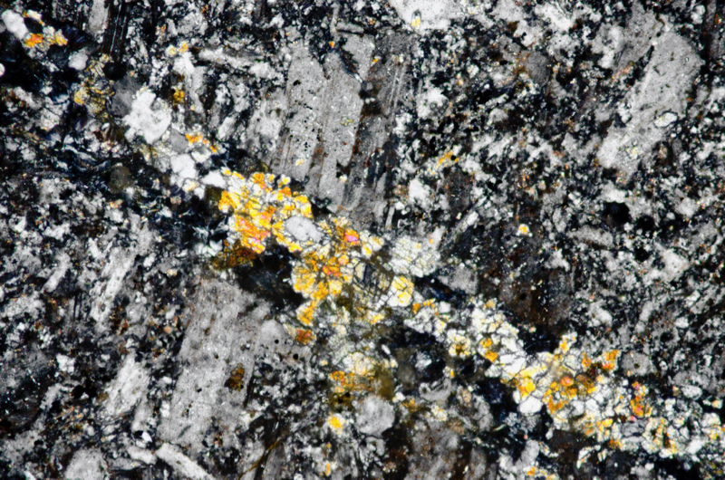 Pyroxene-rich veinlet and fine-grained intrusive material in altered andesite, Dunmoor Hill. Section viewed with crossed polarising filters (FoV 1.2 x 0.8 mm)
