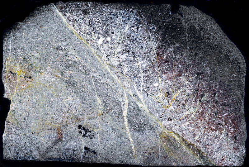 Andesite hornfels with very fine-grained mafic material and pyroxene-rich veinlets, Dunmoor Hill. Thin section viewed with crossed polarising filters (Section measures 30 mm across)